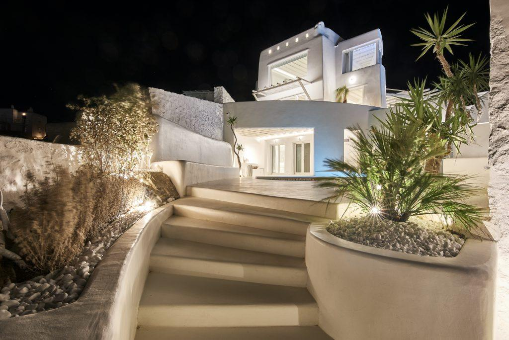 luxury villa with white steps at the entrance leading to the pool