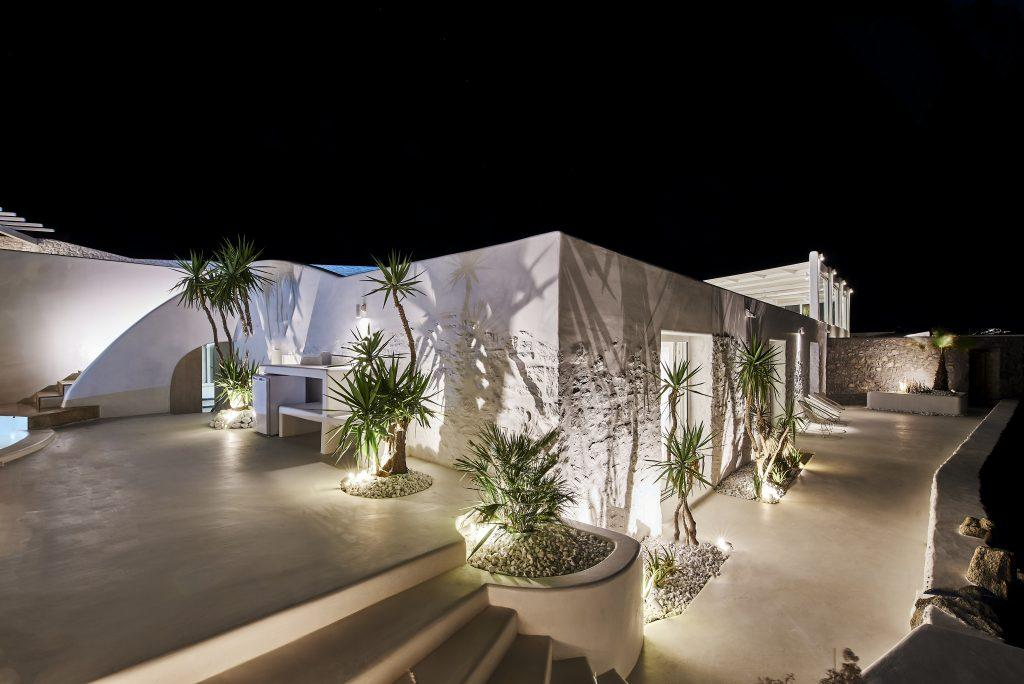 night view of a modernly lit villa decorated with palm trees