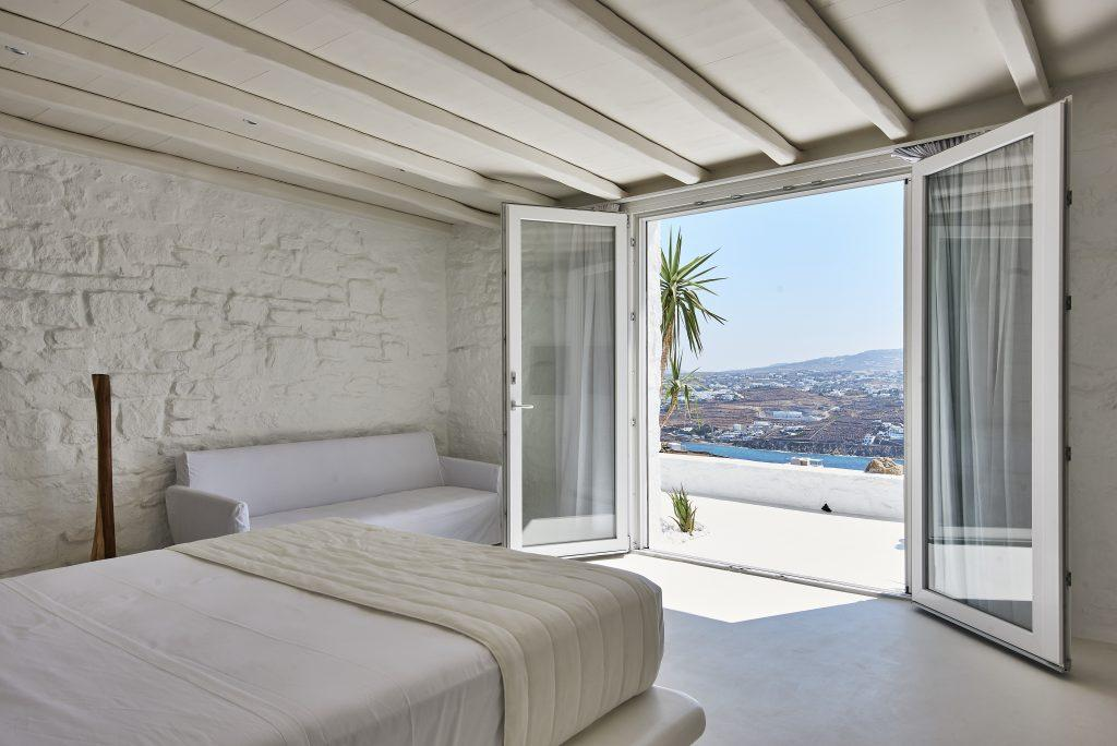 view of the crystal blue sea from the bedroom with white stone walls