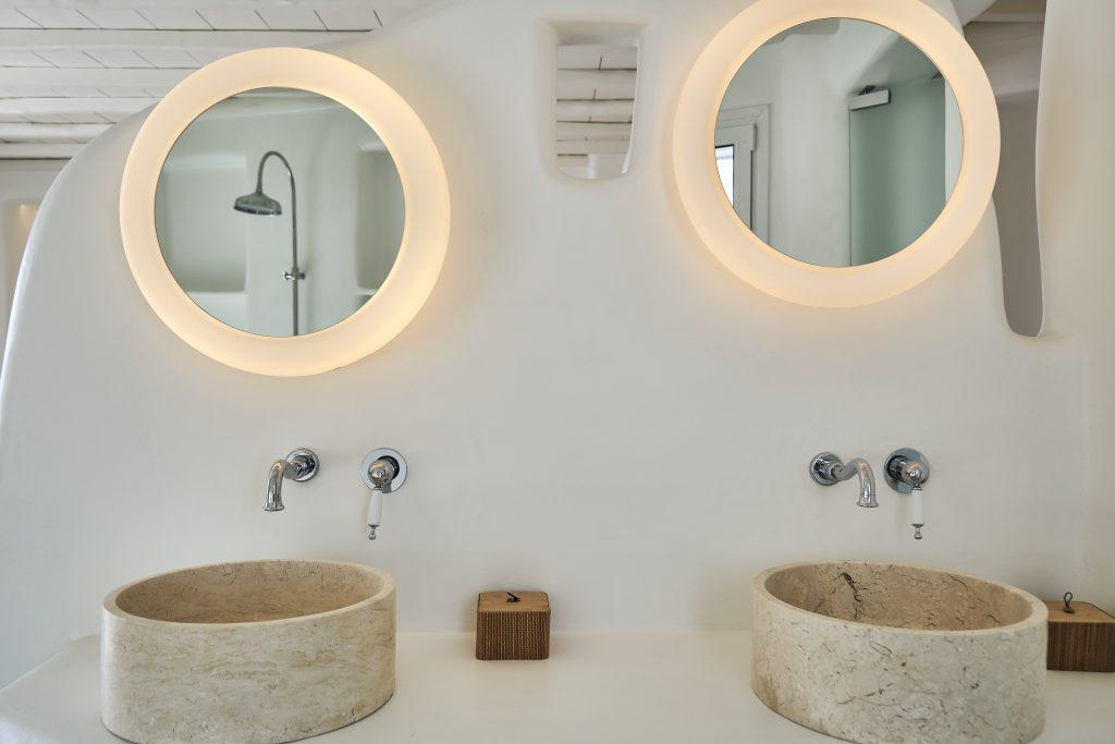 mirrors lit by lamps and a ceramic sink