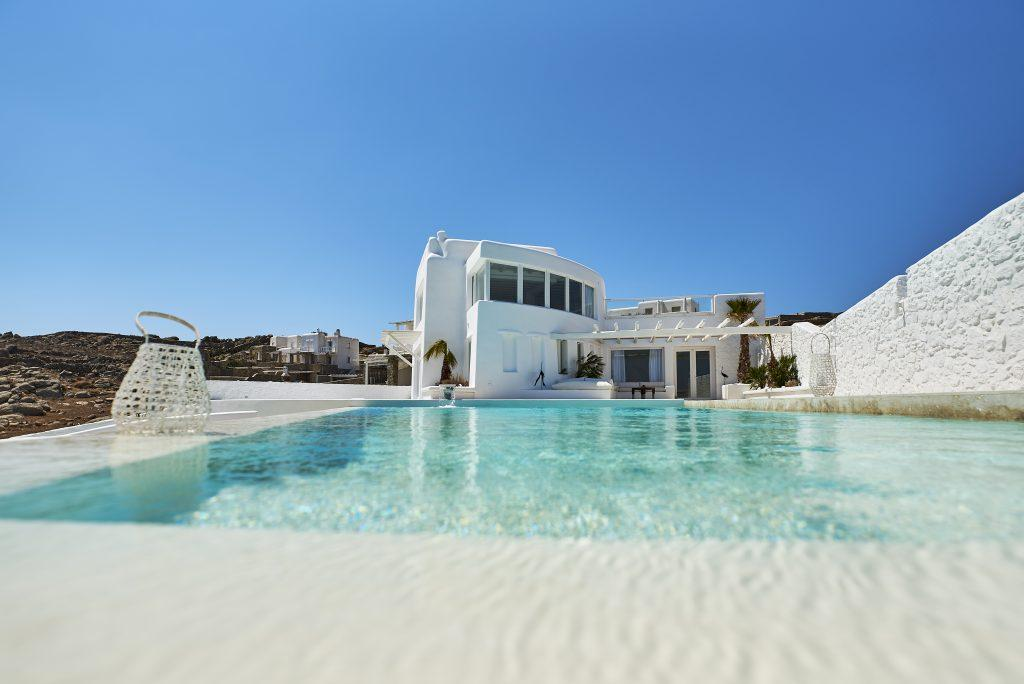view of a luxurious white villa decorated with green palm trees