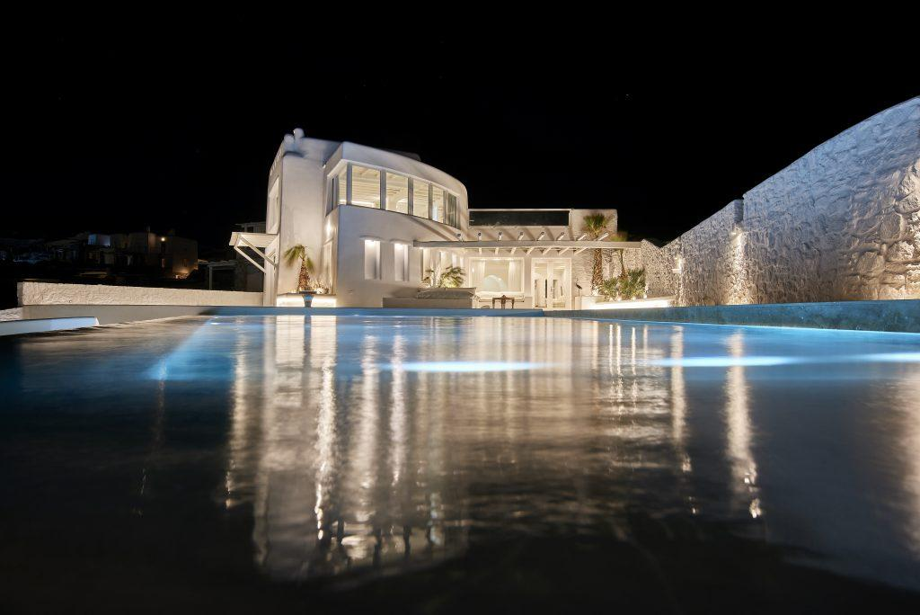 night view from the pool on a luxury villa lit by lamps