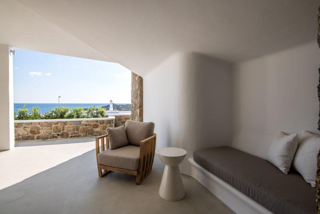 inner terrace with wooden armchair and sofa with stunning view of sea bay horizon and lighthouse