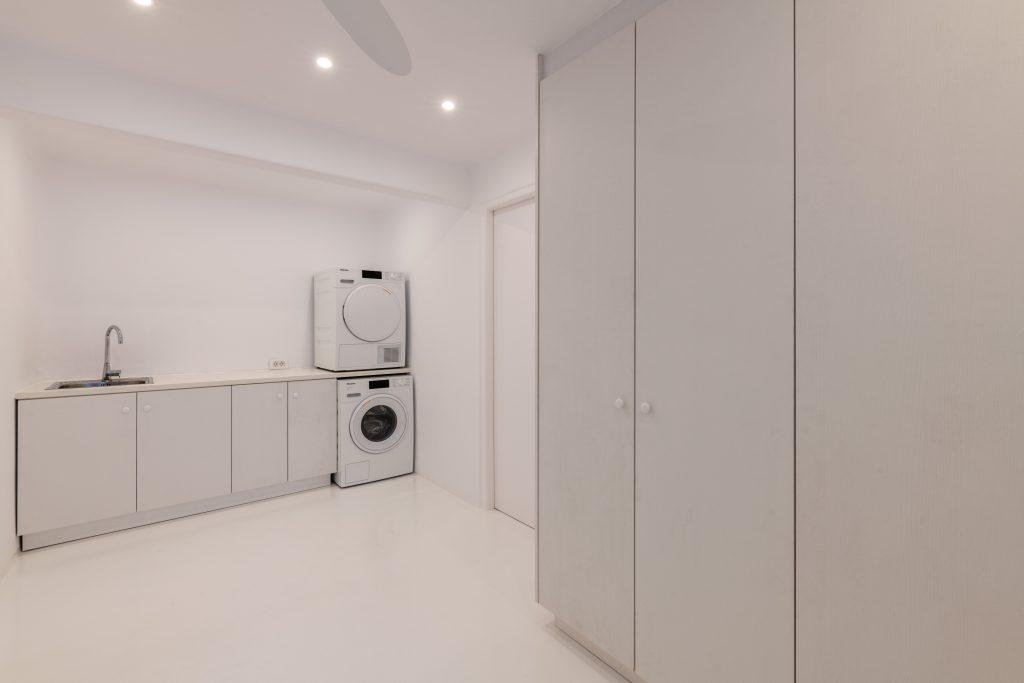 big white painted room with huge closets washing and drying machine and kitchen sink