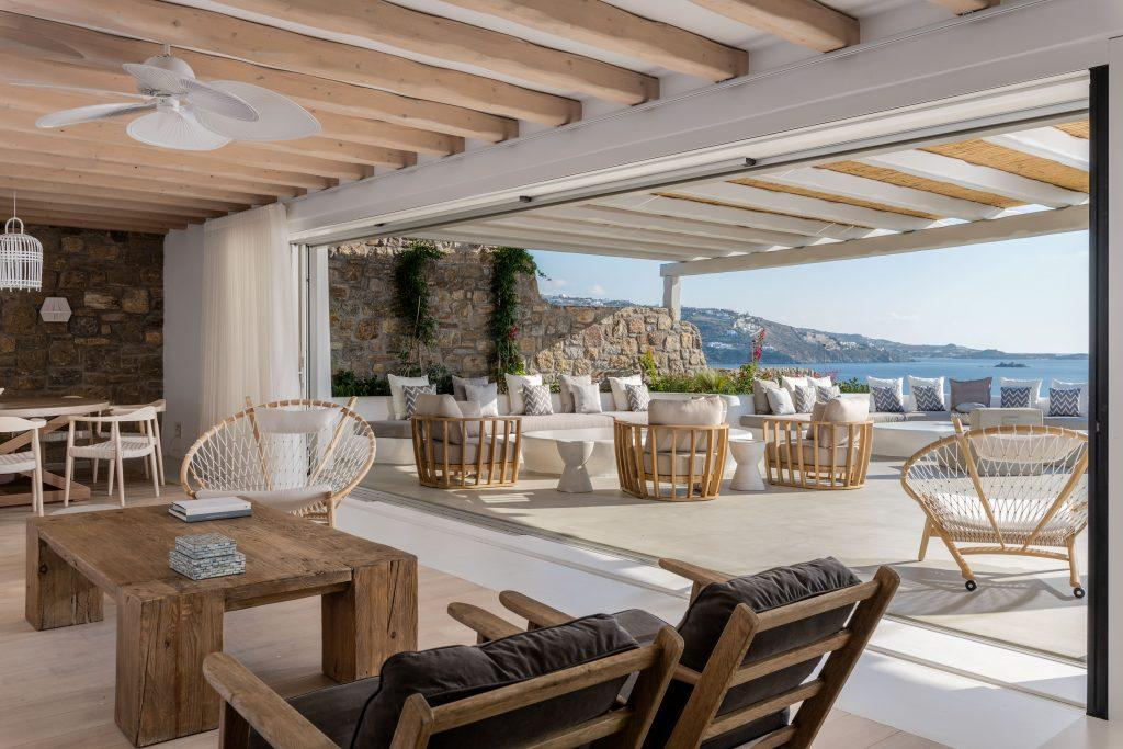 enormous open terrace with sofas armchairs and tables ideal for family and friend gatherings with stunning island cliff and sea view