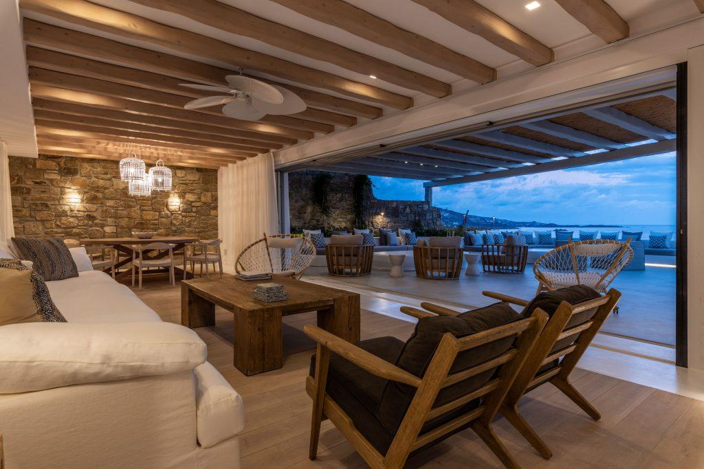 living area with comfy couch wooden armchairs table to enjoy Mykonos island sunset