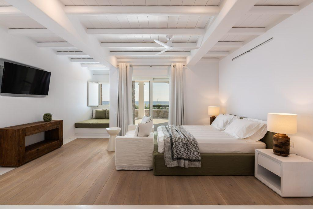 laminate tiled bedroom with cozy bed and night lamps next to it balcony window wall exit and extra corner bed ideal for small kids to stay with their parents