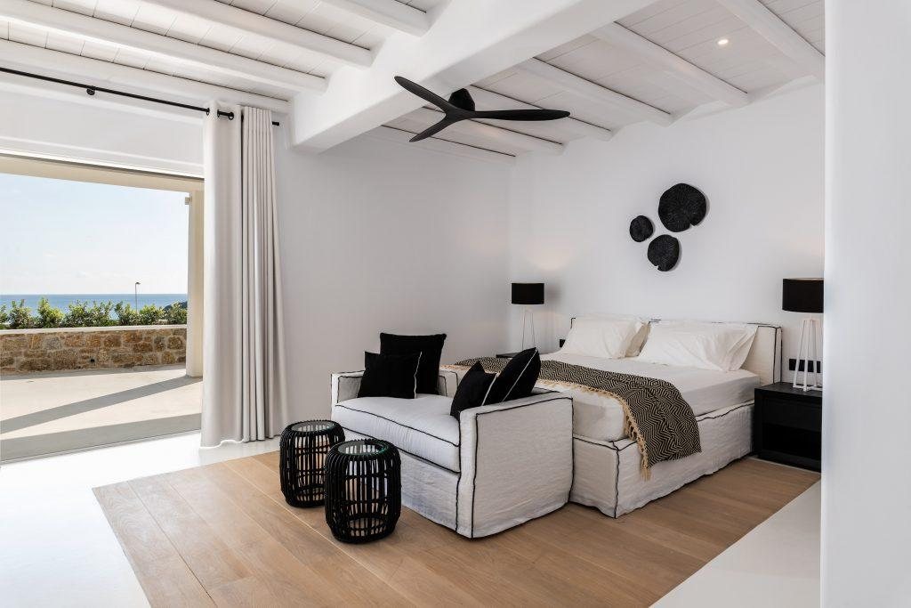 lavish bedroom containing king size bed two black lamp nightstands and balcony walled window