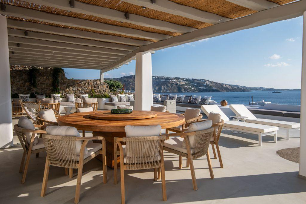 inner part of terrace with enough chairs for all villa quests to sit over the table and enough space on sofas and sunbeds to enjoy Mykonos panorama