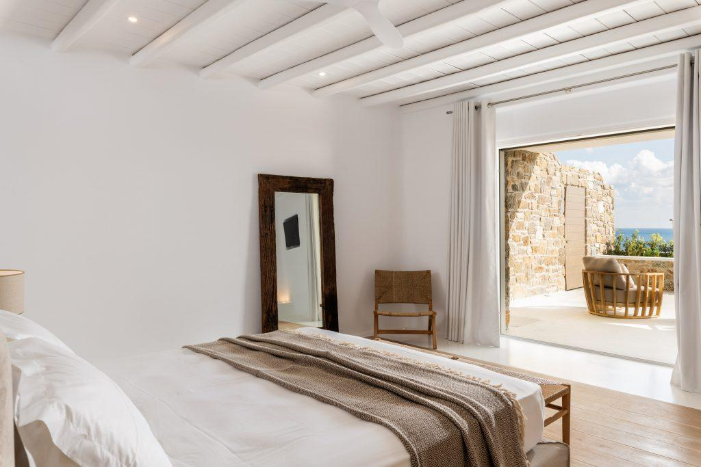 bright and cozy bedroom with wall window sea view wooden chair in the corner