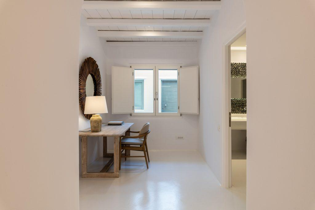 marble paved hallway with wooden desk and chair next to the window