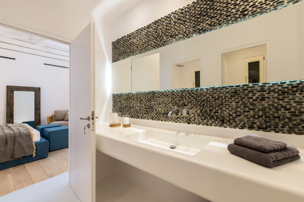 bright lighted bathroom with wide mirror spacious sink and grey towels