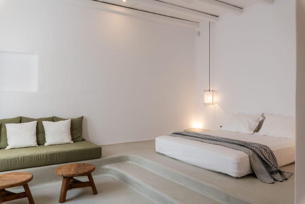 vast and bright bedroom with additional green sofa and two small wooden tables