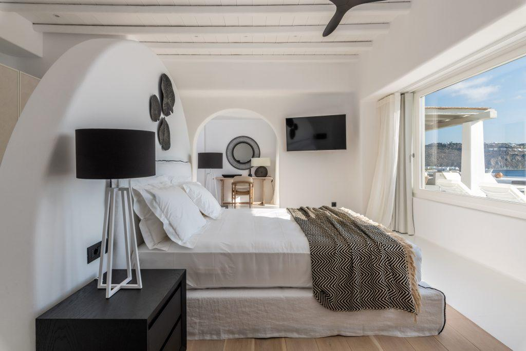 wide double bed with wall mount TV black nightstand black lamp and facing window walled sea view and balcony