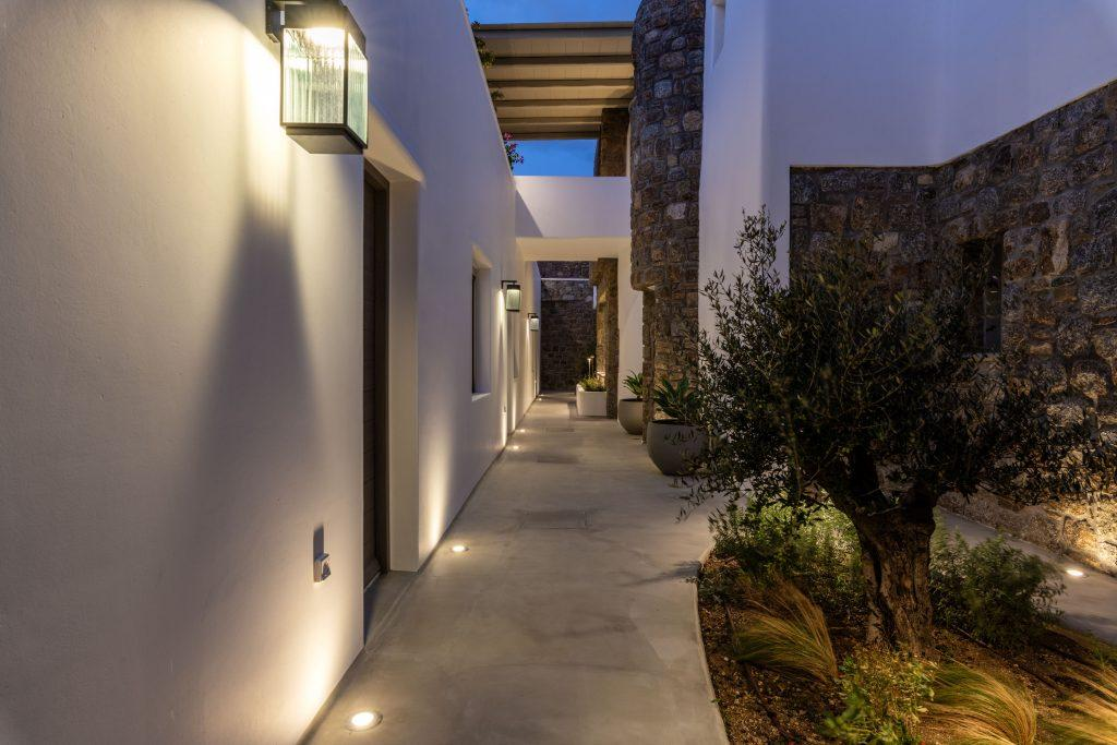 bright lighted outlook of villa exterior with stone wall and small decorative trees