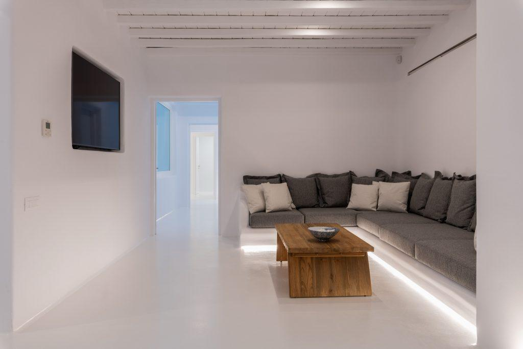 scarce living area with L shaped sofa with enough space wooden table in the middle and wall mounted TV ideal for movie night with your friends