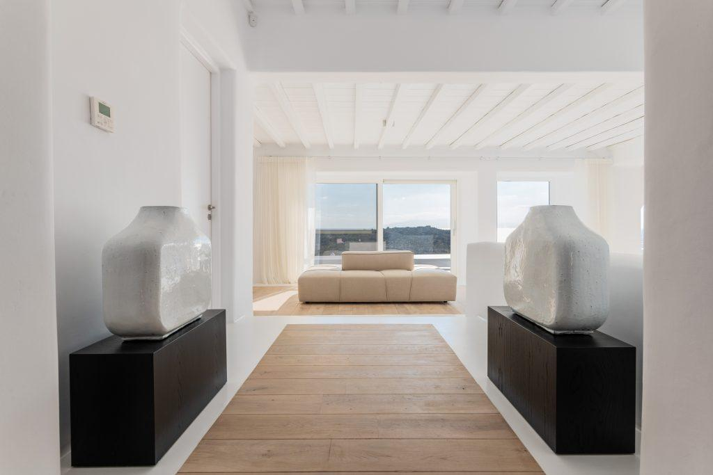 white walls of the room with decorative black shelves and beige furniture