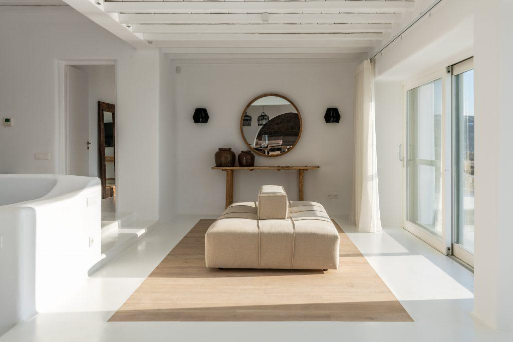 white walls of the room with a round wooden frame mirror and comfortable beige furniture