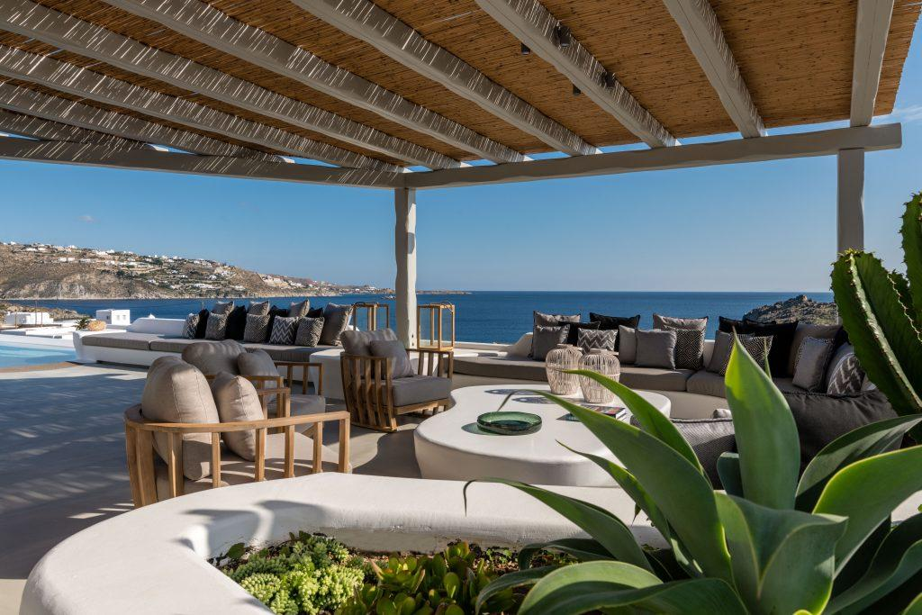 view of the blue sea of Mykonos from the spacious courtyard of the villa decorated with cozy garden furniture