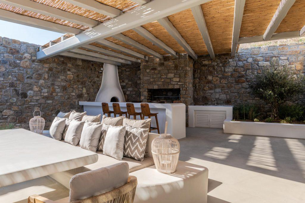 modern white stone bar in the courtyard with a large dining table and a white stone fireplace