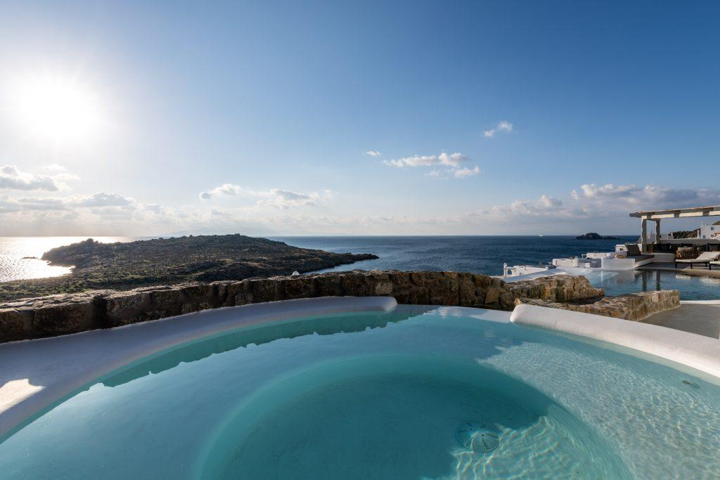 view of the glistening blue sea and nature from the pool of pleasant water