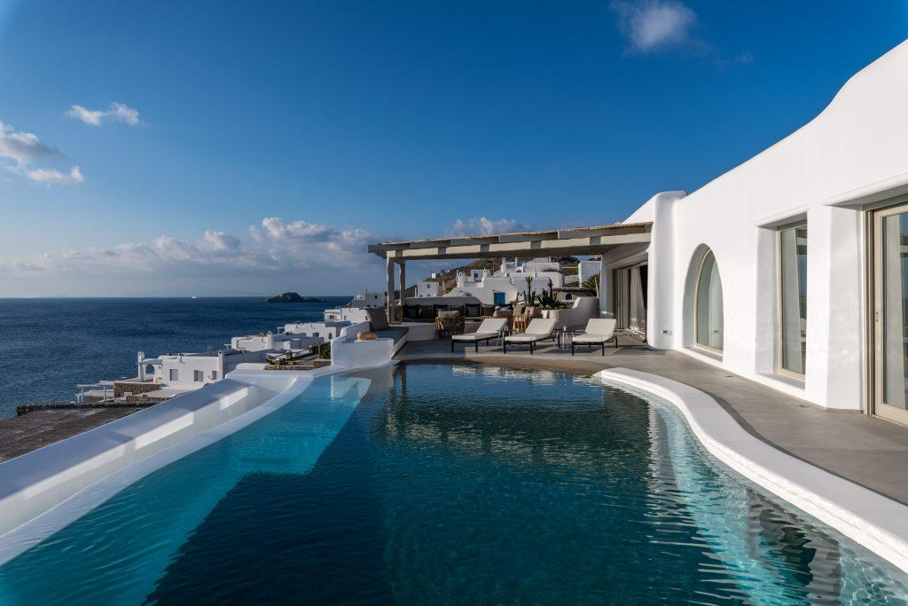 white villa with a pool of pleasant water and cozy deck chairs ideal for enjoying the summer days