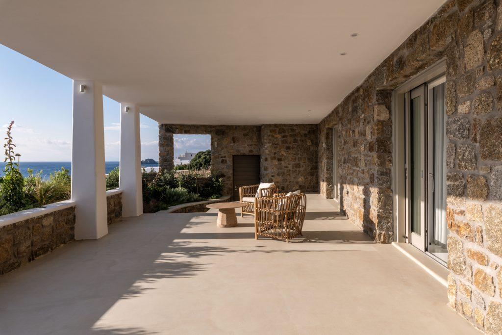 spacious balcony with stone walls and wicker garden furniture
