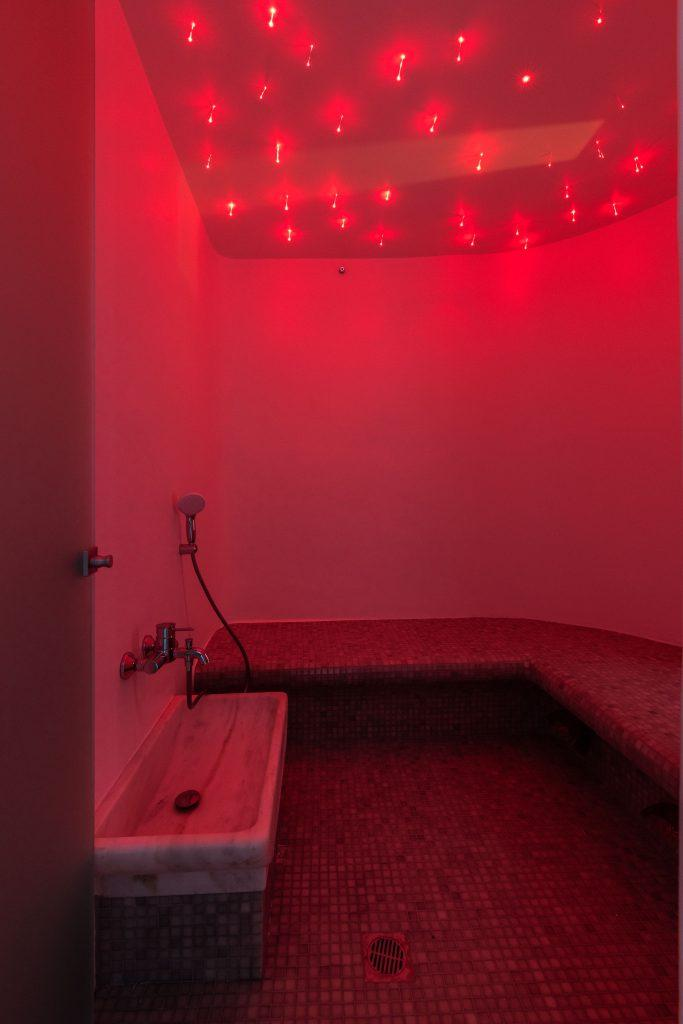 bathroom lit by a red light that contributes to the atmosphere