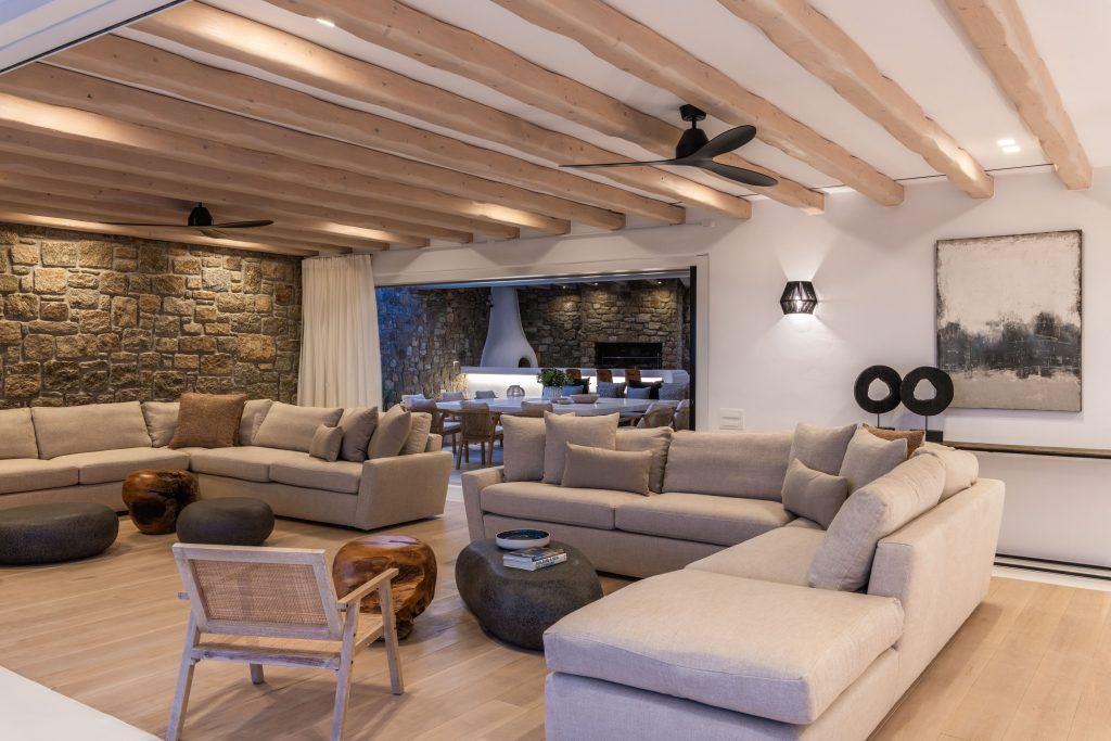 modernly decorated room with a beige corner sofa and a stone decorative wall