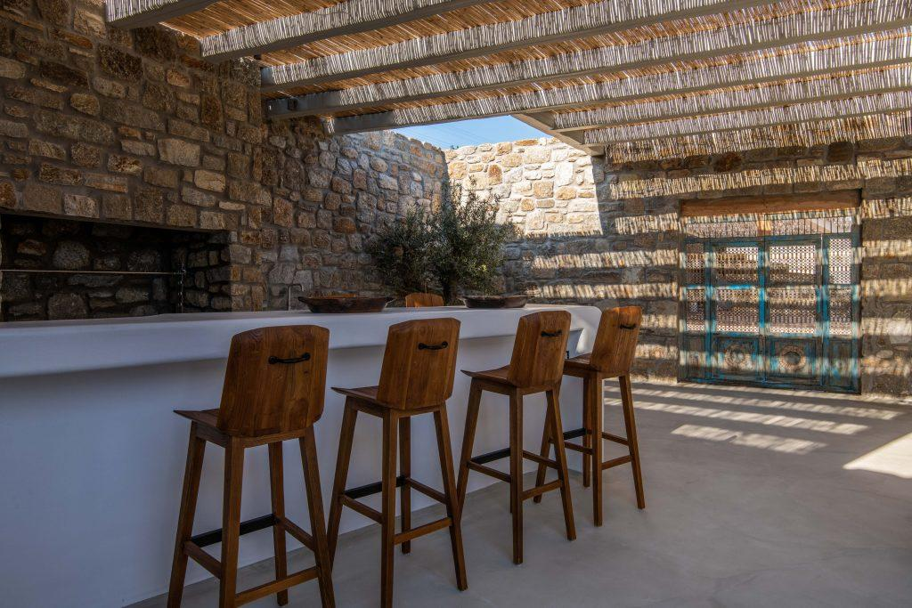 courtyard with white stone bar and wooden chairs