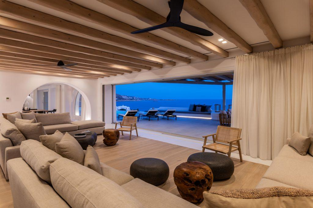 view of the sunset over the blue sea from the living room with cozy furniture