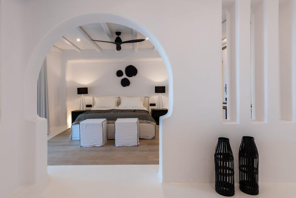 white walls bedroom with decorative black details on the wall and lamps in the corners