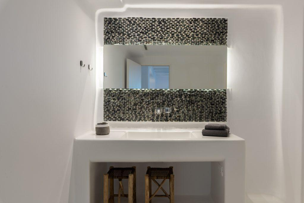white sink with a mirror decorated with stone details