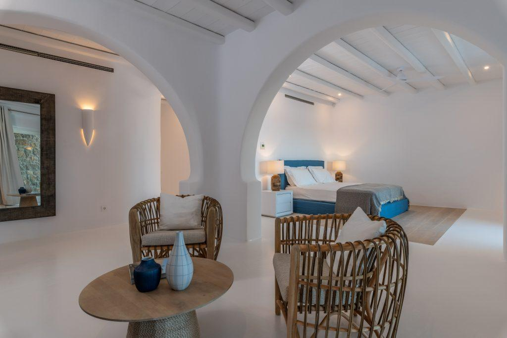 spacious room with white walls for two and a blue bed decorated with comfortable wicker armchairs