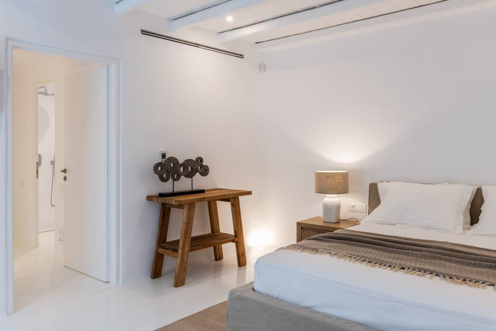 room with white walls and a decorative wooden shelf next to a cozy bed