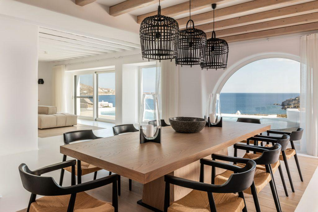 view of the calm clear sea from the dining room with large windows that provide daylight