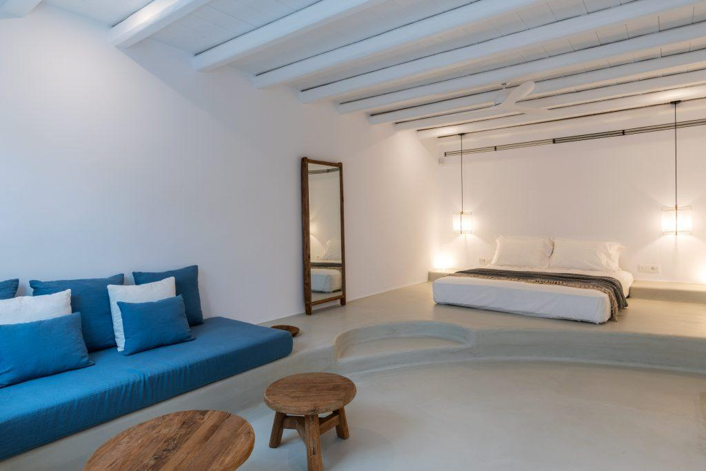 white bedroom walls with a large wooden frame mirror and blue comfortable furniture