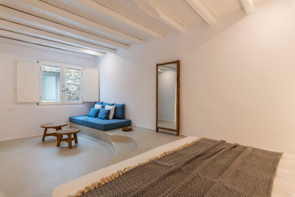 white bedroom walls with a large wooden frame mirror and blue comfortable pillows