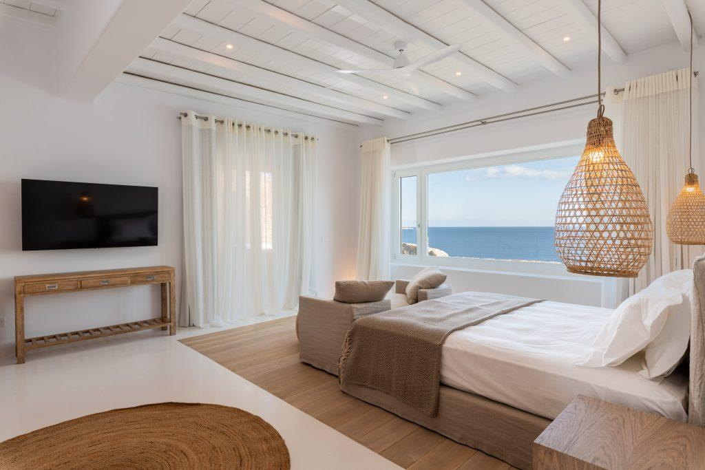 view of the light blue sea from the spacious bedroom with white walls and lots of daylight