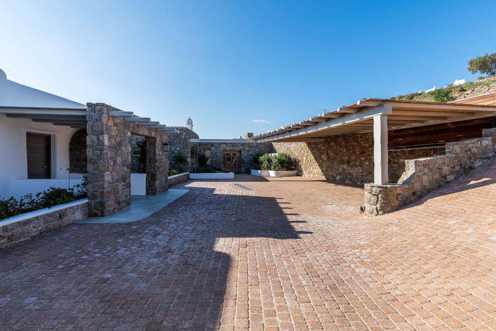 private parking with wooden canopy and stone walls