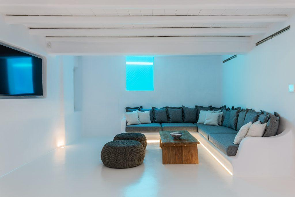 dimly lit room with white walls and gray furniture