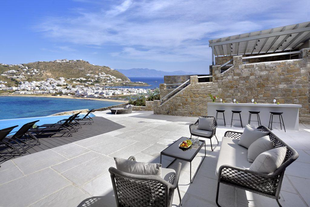 comfortable garden furniture by the pool overlooking the glistening sea