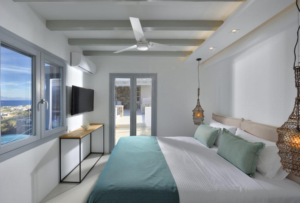 view of the light blue sea from the bedroom for two with cozy king size bed