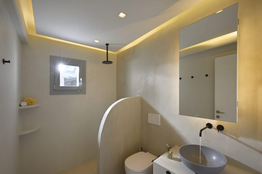 white bathroom walls with shower and circular sink