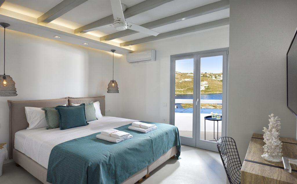 view of the light blue sea from the bedroom with king size bed