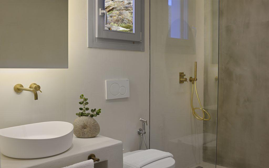 modernly designed white-walled bathroom with shower and ceramic circular washbasin