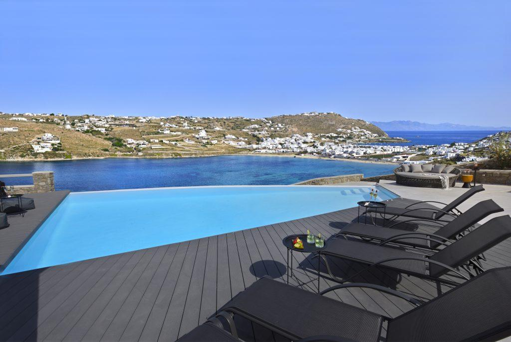 view of the beautiful blue sea that shines under the sunny sky from the pool of pleasant water