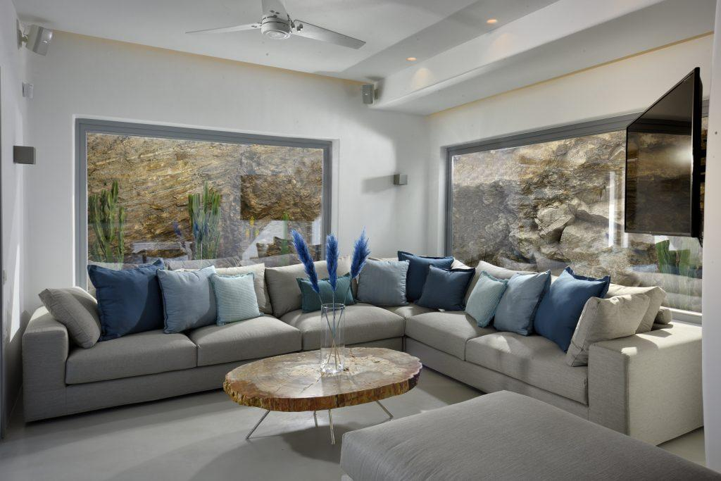 living room with comfortable gray furniture and a wooden table decorated with blue details