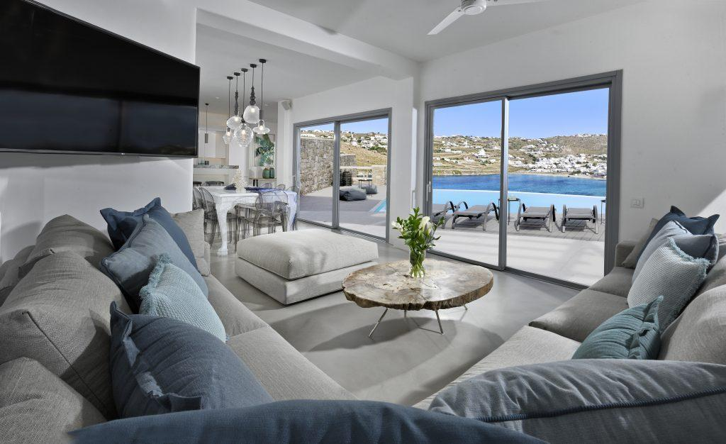 living room with large terrace door and views of the luxurious courtyard with pool