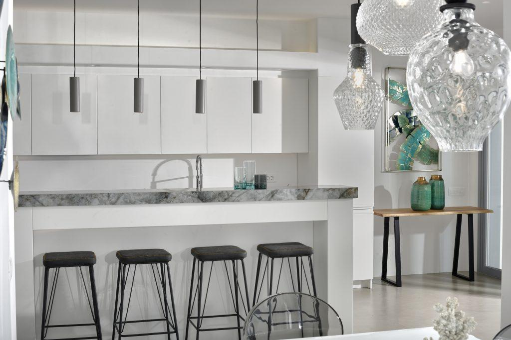 modernly designed kitchen with white high-gloss elements decorated with blue vases